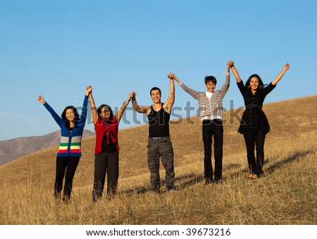 Group of young asian people holding hands and smiling - stock photo