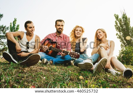 group of young attractive best friends having fan together. playing on the guitar, singing and laughing.