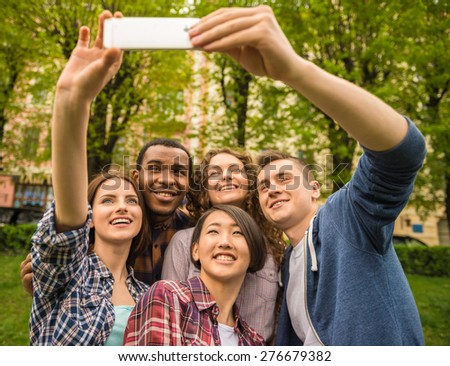 Group of young attractive smiling students dressed casual making selfie outdoors on campus at the university. - stock photo