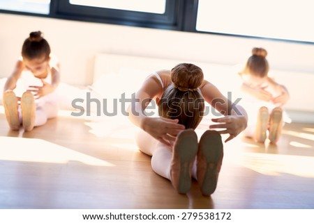 Group of young ballerinas in class doing stretching exercises seated on the wooden floor as they warm up before practice to increase their suppleness - stock photo