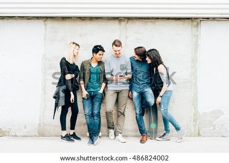 Group of young beautiful multiethnic woman and man friends leaning against a wall outdoor in the city using smart phone - technology, social network, friendship concept