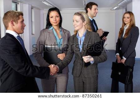 Group of 5 young business people, handshake welcome gesture, office shoot - stock photo
