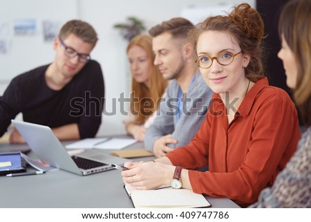 Group of young business people in a team meeting sitting around a table in the office with focus to a young woman looking at the camera with a smile - stock photo