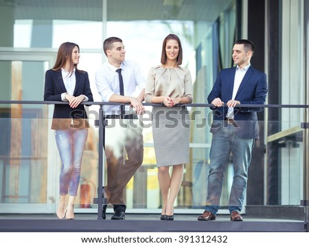 Group of young business people is spending time together on a coffee break in front of the office. Young woman is looking at camera and smiling and her colleagues are looking at her. - stock photo