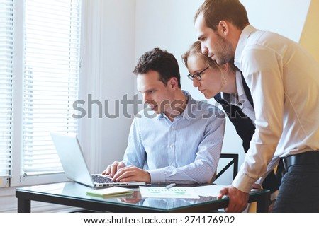 group of young business people looking at the screen of computer - stock photo