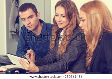 Group of young business people on a meeting exchanging ideas - stock photo