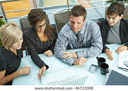 Group of young business people sitting around table on office terrace outdoor, talking and working together. Overhead view. - stock photo