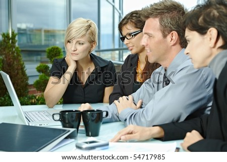 Group of young business people sitting in a row at table on office terrace outdoor, talking and working on laptop computer. - stock photo