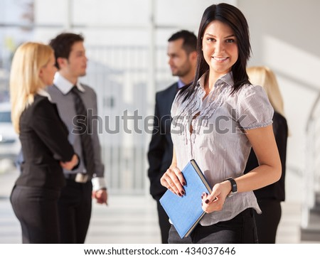 Group of young business people standing in they office.Woman standing in front.
