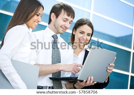 Group of young business people work with the laptop against modern office building - stock photo