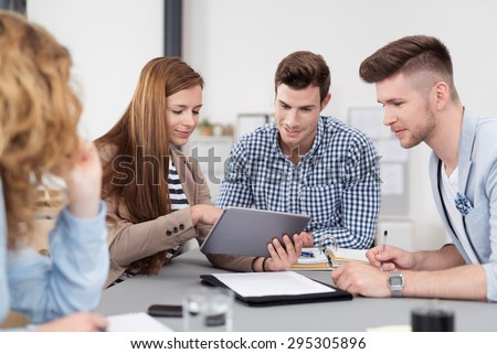 Group of Young Businesspeople Having a Meeting In the Boardroom and Using Tablet Computer for Presentation.