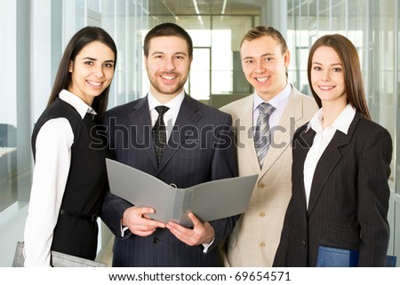 Group of young businesspeople smile and look at the camera - stock photo