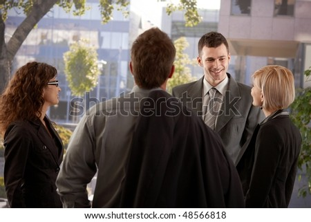 Group of young businesspeople talking in front of of office building. - stock photo