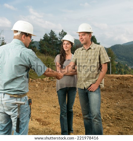 group of young caucasian architects shaking hands on construction site - stock photo