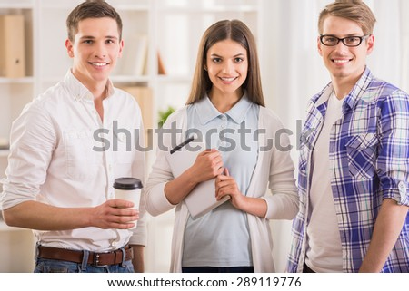 Group of young colleagues dressed casual standing together in modern office. - stock photo