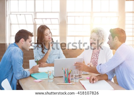 Group of young colleagues using laptop in a meeting against inside a building - stock photo
