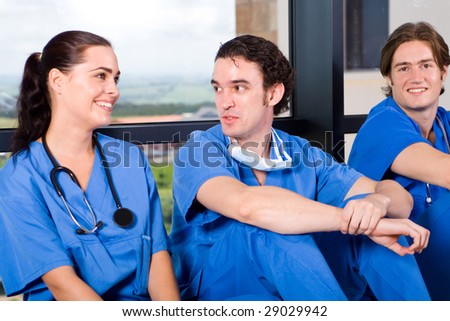 group of young doctors and nurses relaxing in hospital hallway during break - stock photo