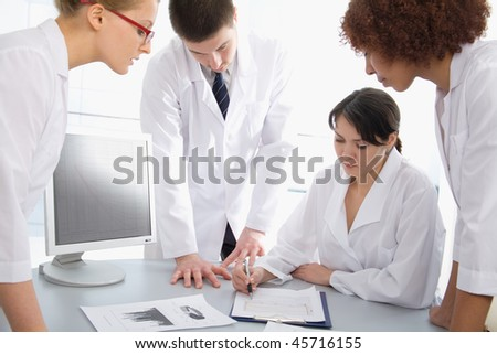 Group of young doctors discuss work - stock photo