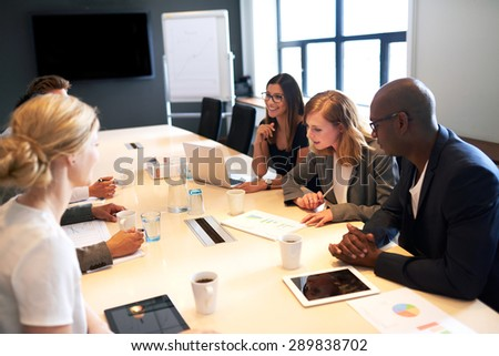 Group of young executives holding a meeting in a conference room - stock photo