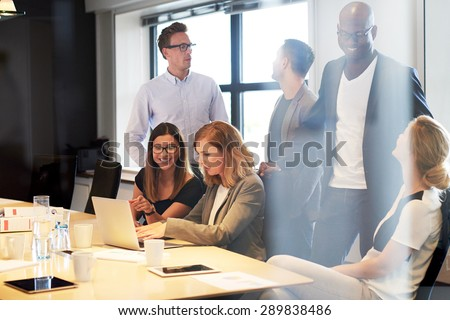 Group of young executives socializing in office conference room - stock photo