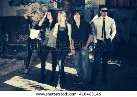 Group of young fashion men and women against graffiti wall. Male and female stylish model indoors