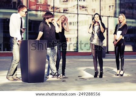 Group of young fashion men and women calling on mobile phones