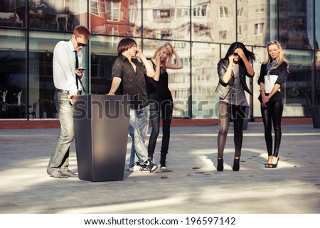 Group of young fashion men and women calling on the phones