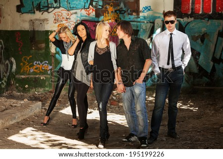 Group of young fashion people at the graffiti wall