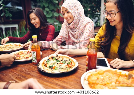 Group Of Young Friends Enjoying Meal In Outdoor Restaurant - stock photo
