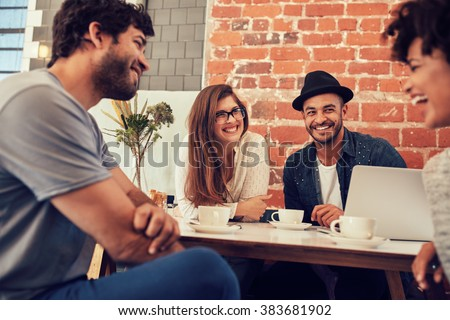 Group of young friends hanging out at a coffee shop. Young men and women meeting in a cafe having fun. - stock photo