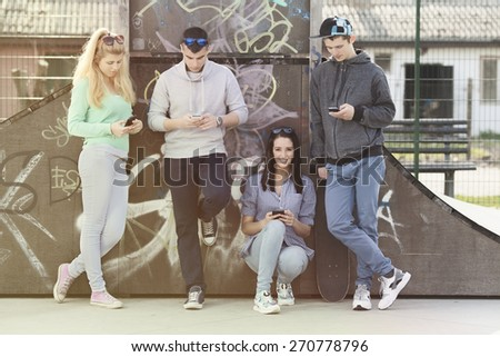 Group of young friends hanging out in a skate park. Portrait of pretty girl holding her mobile phone and smiling - stock photo