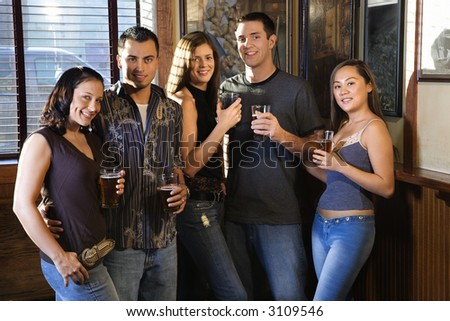 Group of young friends hanging out in pub and drinking beer.