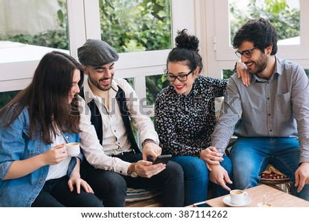 Group of young friends having fun with a cellphone in a cafe bar - stock photo