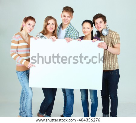 Group of young friends holding a blank board, isolated on white background - stock photo