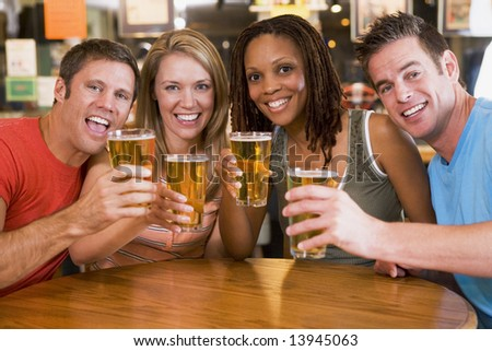 Group of young friends in bar toasting the camera - stock photo