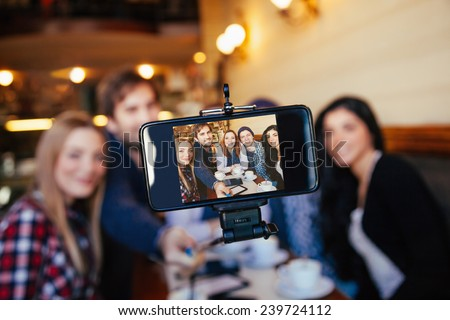Group Of Young Friends In Cafe Taking Selfie Using Smart Phone And Monopod. Focus Is On Smart Phone - stock photo