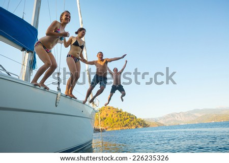 Group of young friends jumping from the yacht into sea - stock photo