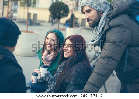 Group Of Young Friends Outdoors Drinking Hot Beverage And Using Technology - stock photo