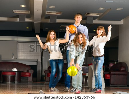 Group of young friends playing bowling, spending time with friends - stock photo