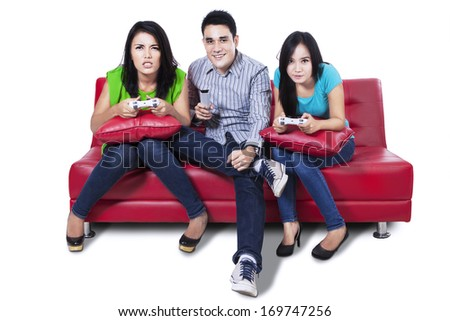 Group of young friends playing video games sitting on red sofa