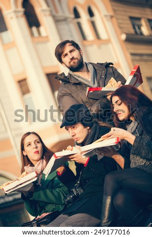 Group Of Young Friends Sitting On Bench And Eating Pizza