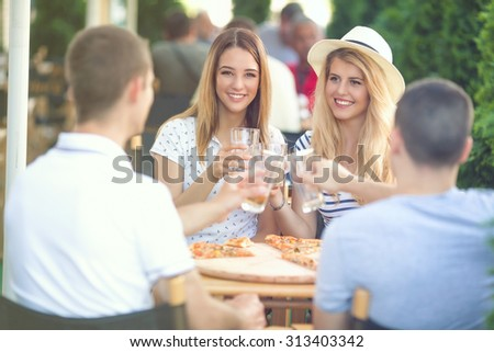 Group of young friends toasting with drinks while eating pizza at the outdoor cafe