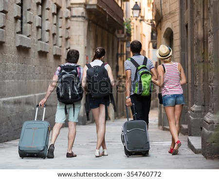 Group of young friends walking through the city with travel bags. Back view - stock photo