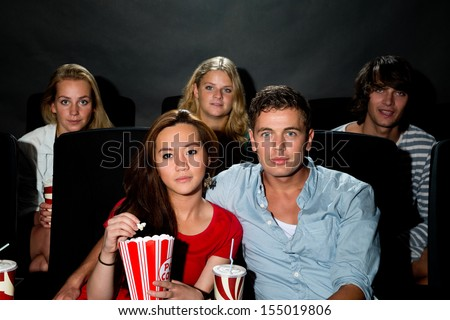 Group of young friends watching a movie at a cinema