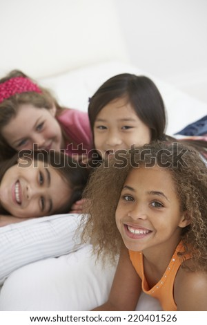 Group of young girls lying on bed - stock photo