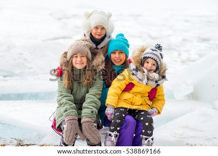 Group of young girls sitting at the ice block on the frozen lake. Outdoors