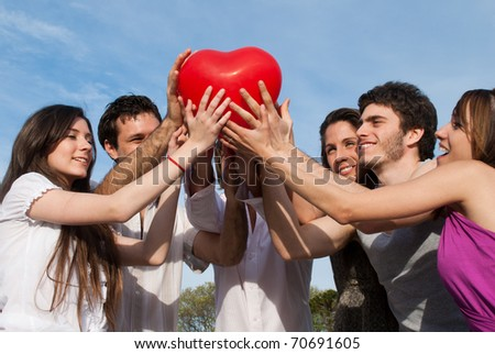 Group of young guys and girls with a sphere in the form of heart - stock photo