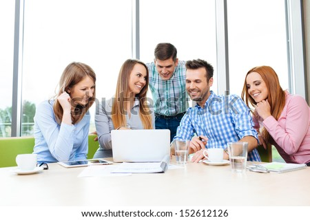 Group of young happy employees working together with laptop - stock photo
