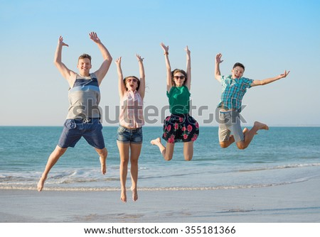 Group of young happy friends have fun  on the beach together jumping up at sunset