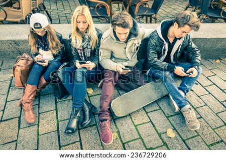 Group of young hipster friends using smart phone with disinterest on each other - Modern situation of technology addiction in alienated lifestyle - Internet wifi connection on vintage filtered look - stock photo
